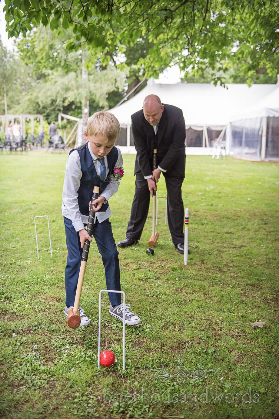 Child wedding guest shows adult how to play croquet at The Old Vicarage Wedding lawn games