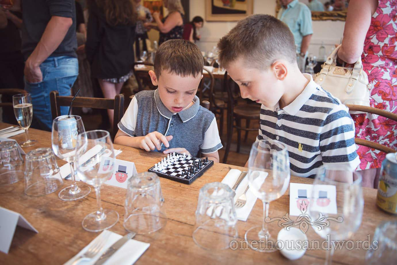 Children wedding guests play travel chess at pre-wedding meal in Swanage