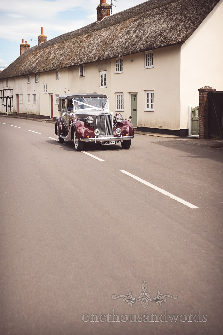 Classic Daimler wedding car outside thatched countryside cottage in Dorset