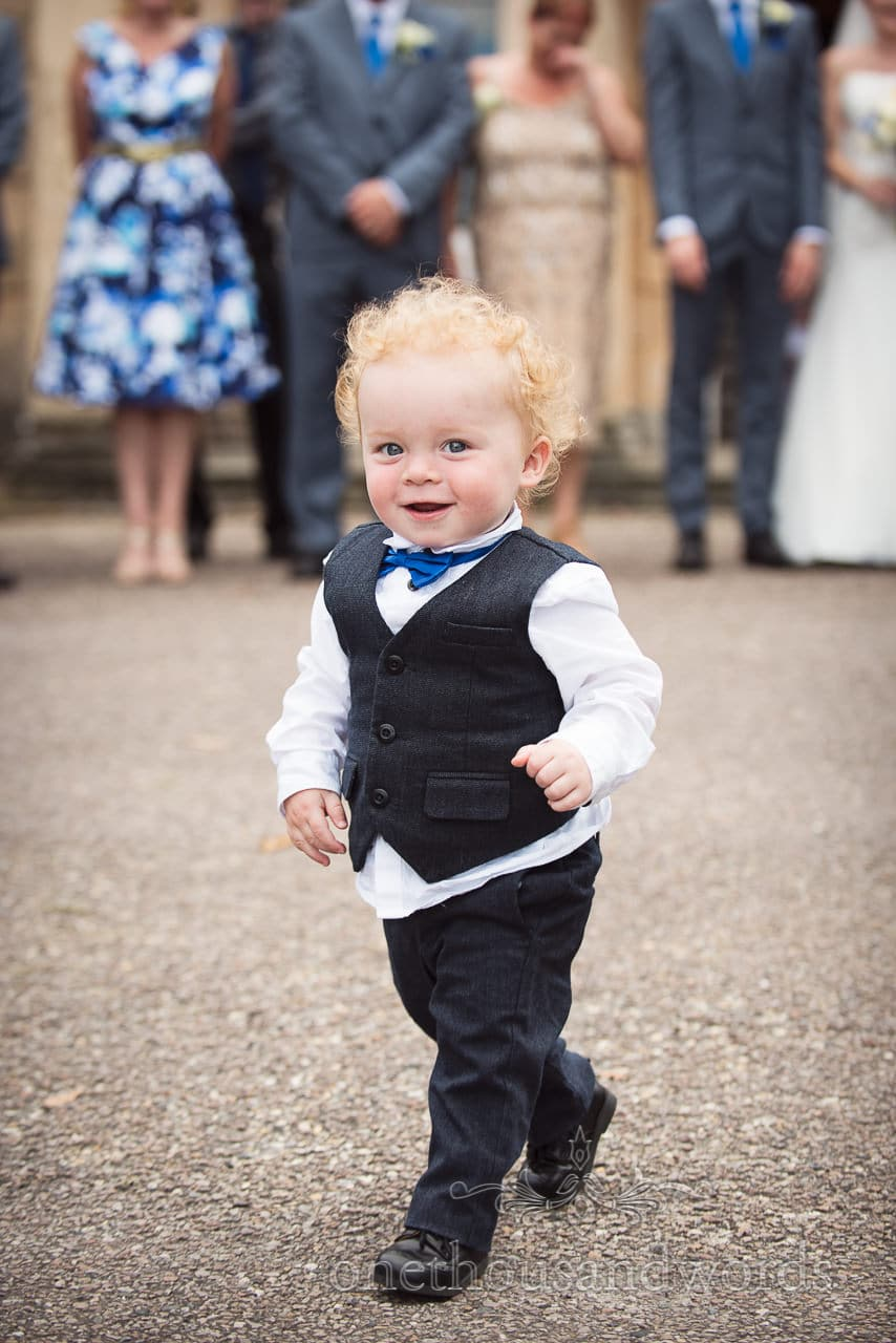 Cute child page boy in wedding suit with blue tie at Upton House wedding in Dorset