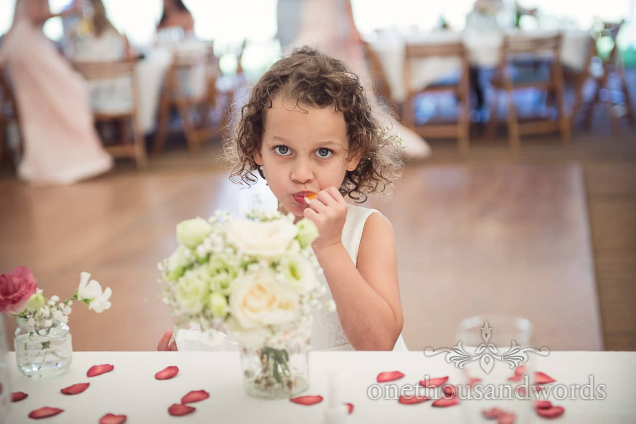 Cute flower girl in white dress eats wedding sweets at countryside marquee wedding