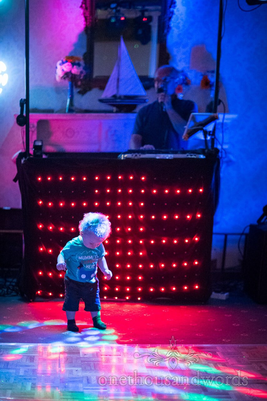 Cute toddler fascinated by disco lights on wedding dance floor at Upton House