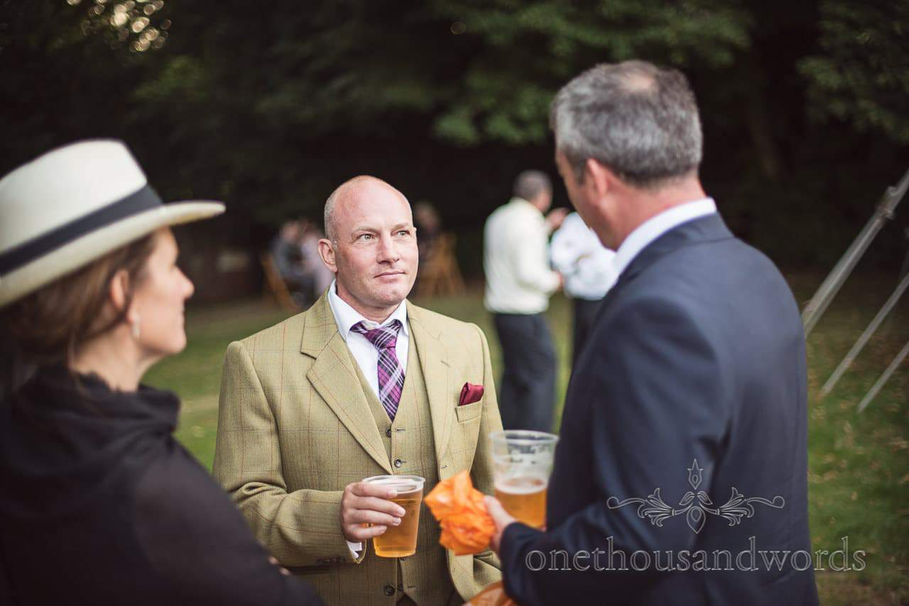 Dapper wedding guest in three piece suit drinks beer at countryside wedding