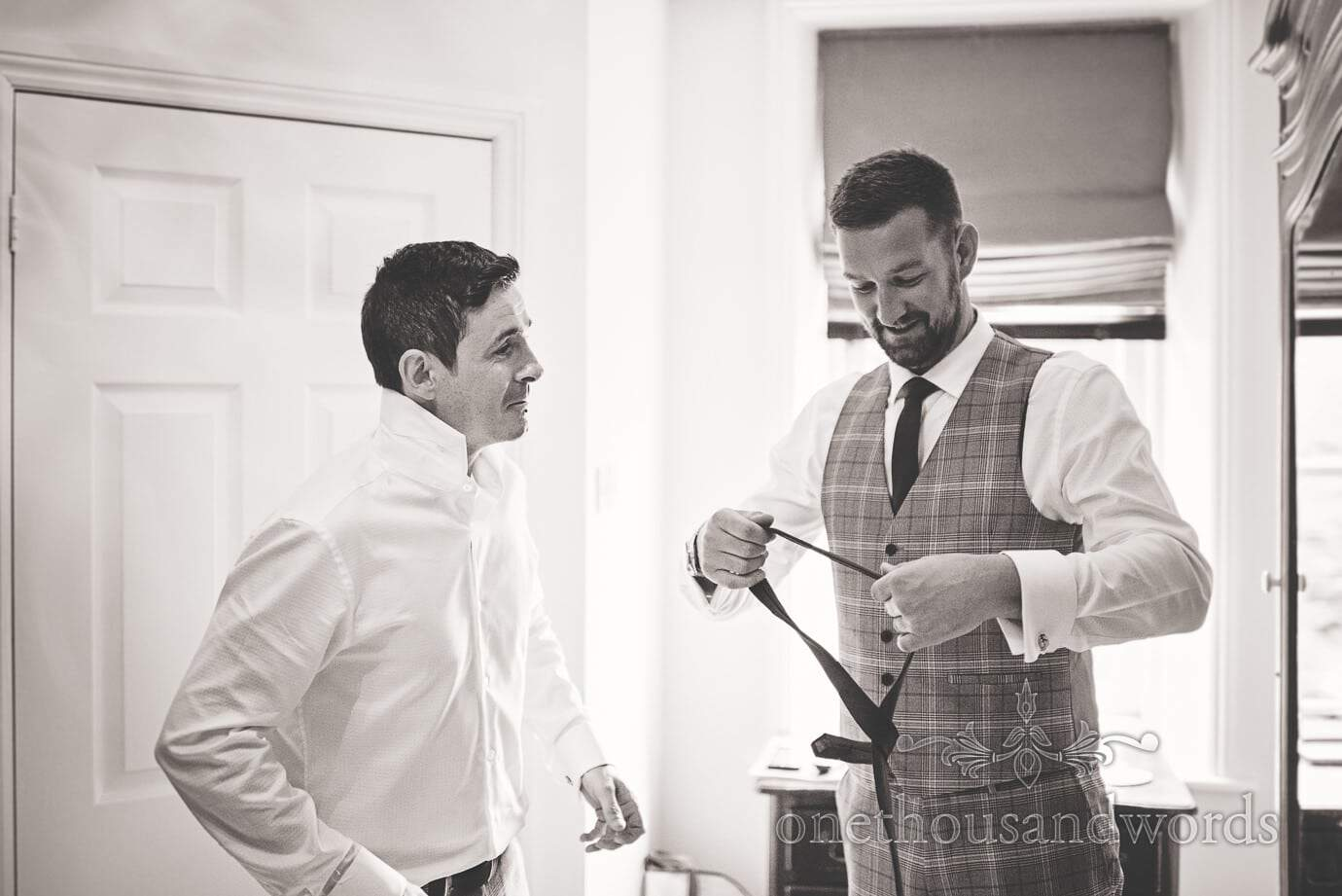Documentary photo of groom and best man preparations in prince of Wales check suit