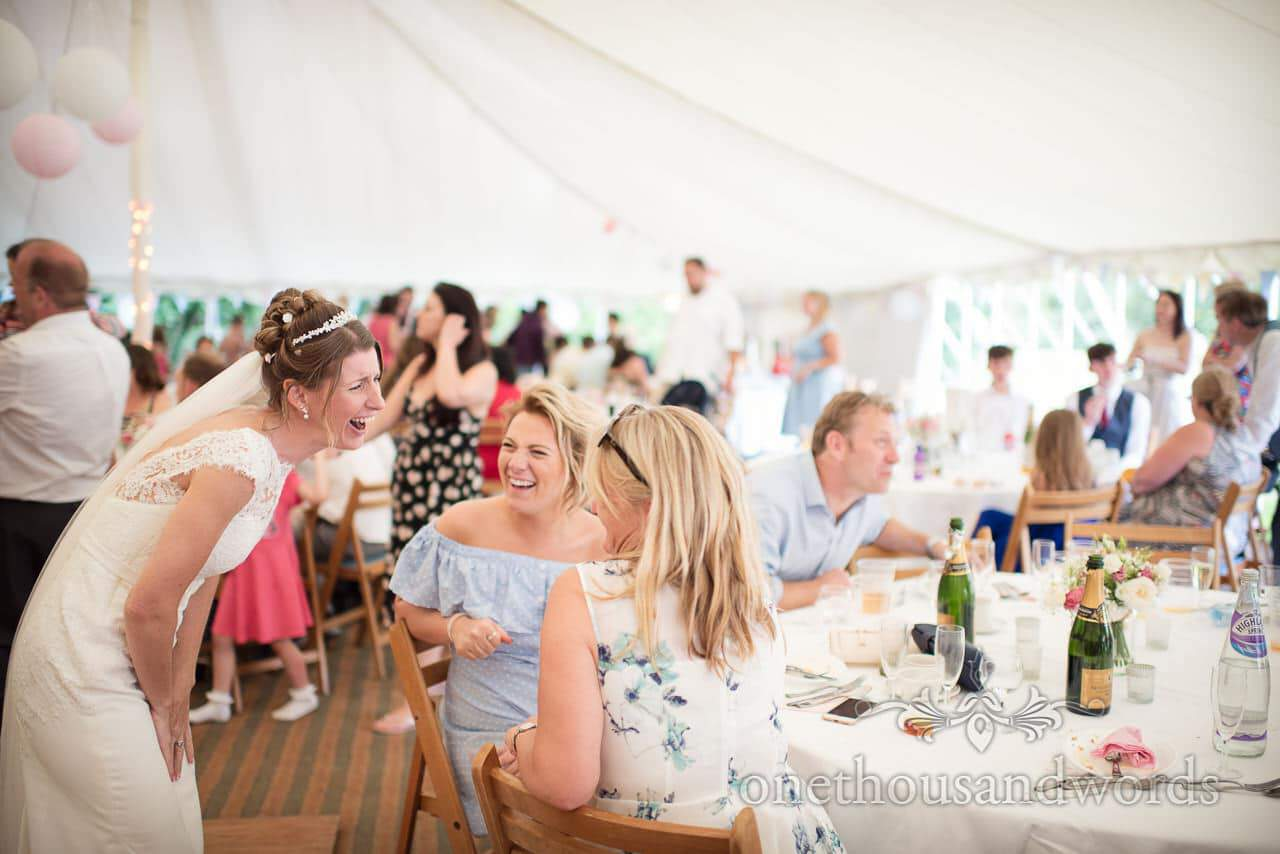 Documentary wedding photograph of bride laughing with wedding guests in marquee
