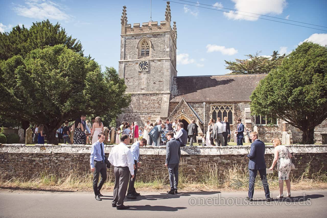 Dorset countryside stone church wedding venue with wedding guests outside