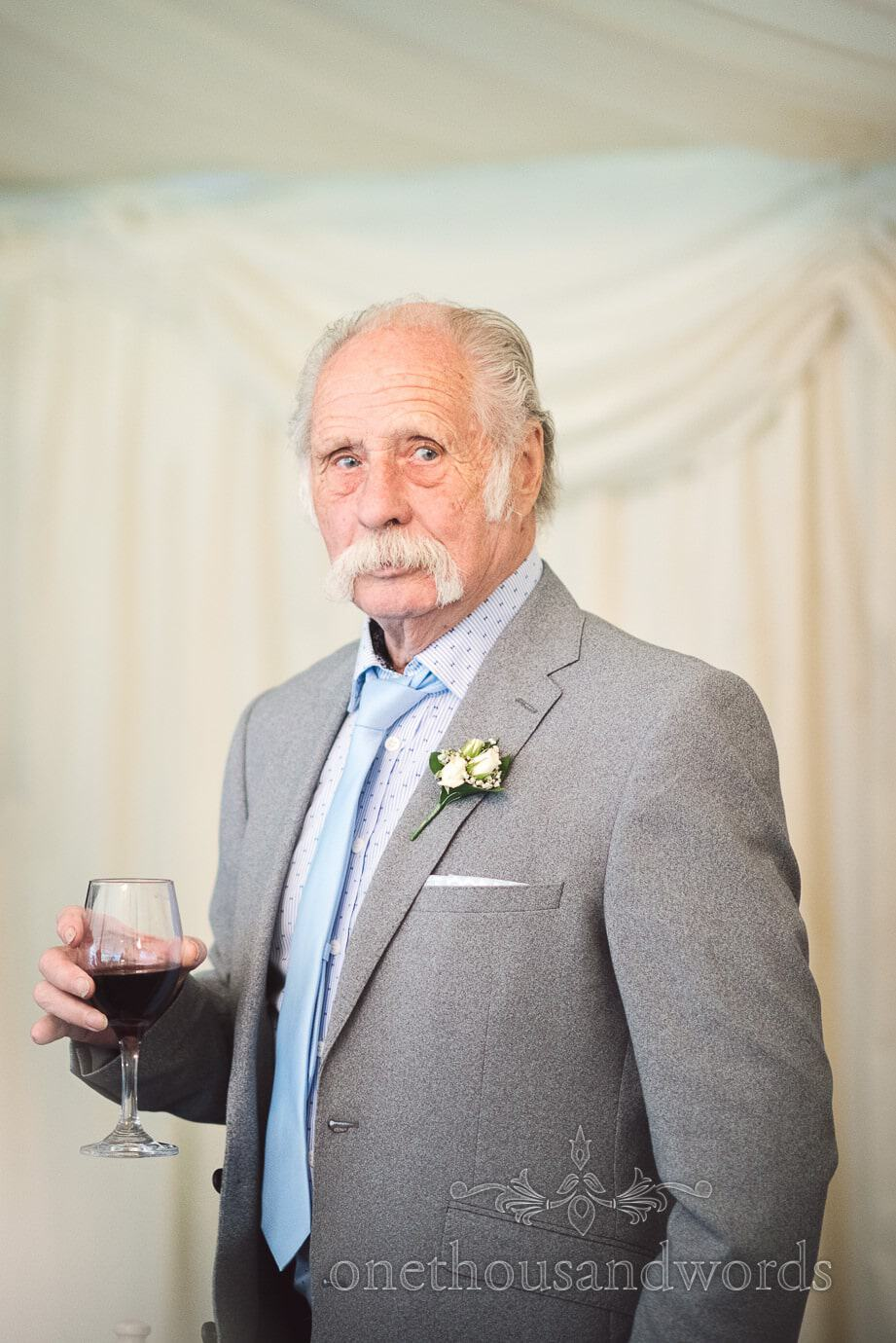 Elderly wedding guest portrait photograph with amazing moustache drinks red wine