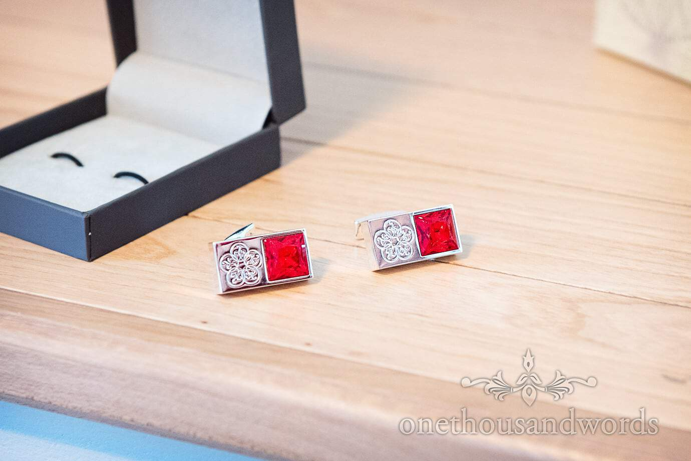 Engraved silver wedding cufflinks with red gems stones on wooden shelf