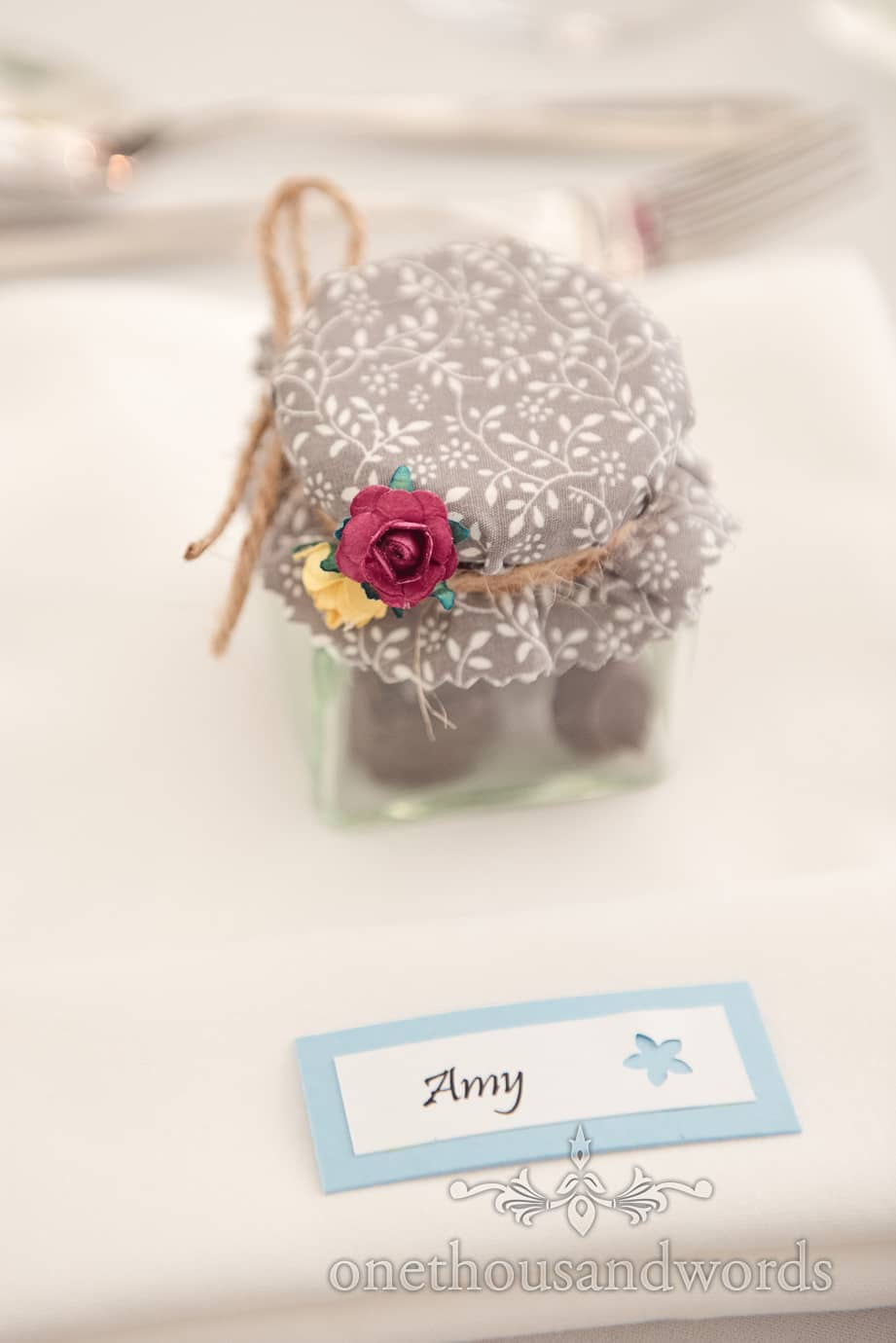 Fabric rose detail on wedding favour jam jars with home made chocolates and name sign