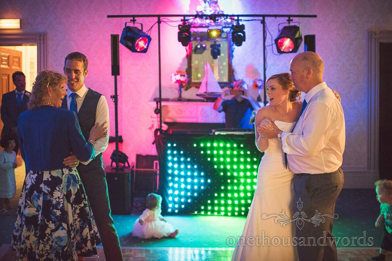 Father dances with bride as mother dances with groom at wedding evening disco