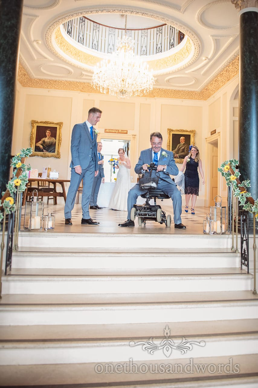 Father of groom pulls wheelie on mobility scooter at top of stairs at Upton House wedding