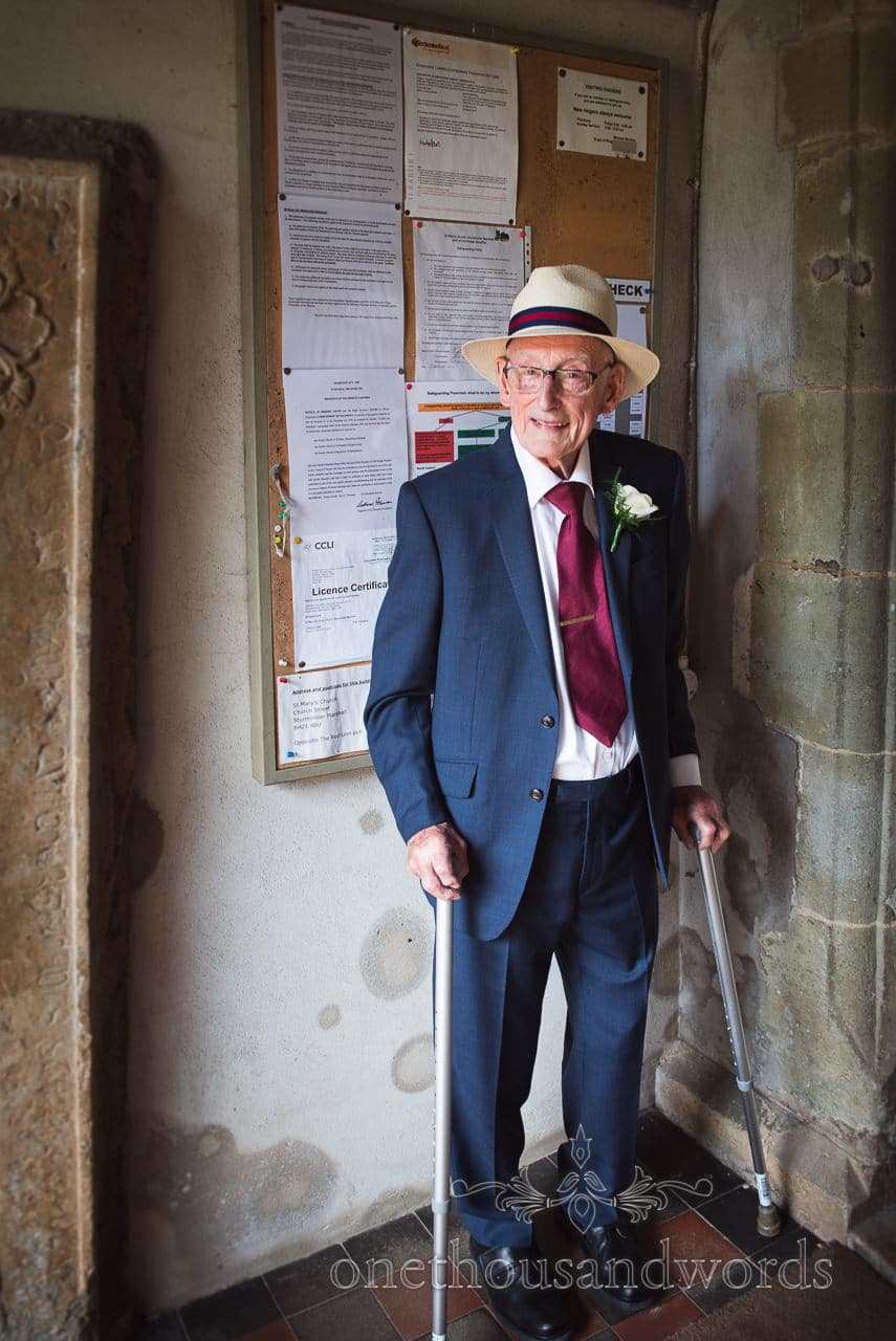 Father of the bride in blue wedding suit and fedora sun hat with crutch