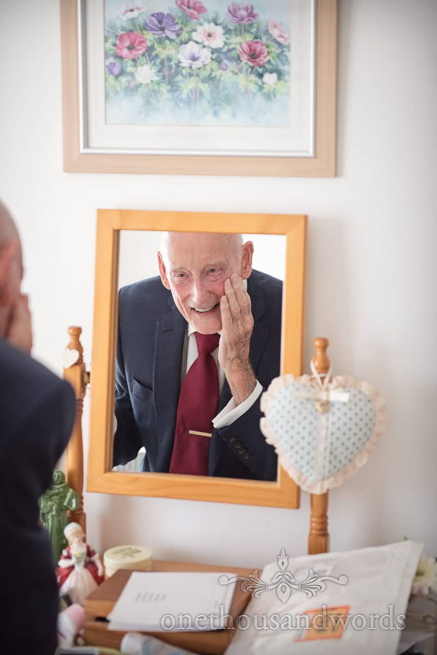 Father of the bride in red wedding tie looks in mirror on wedding morning