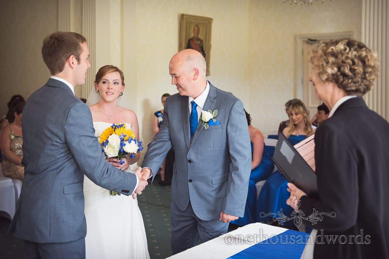 Father of the bride shakes groom's hand as he gives his daughter away at Upton House wedding