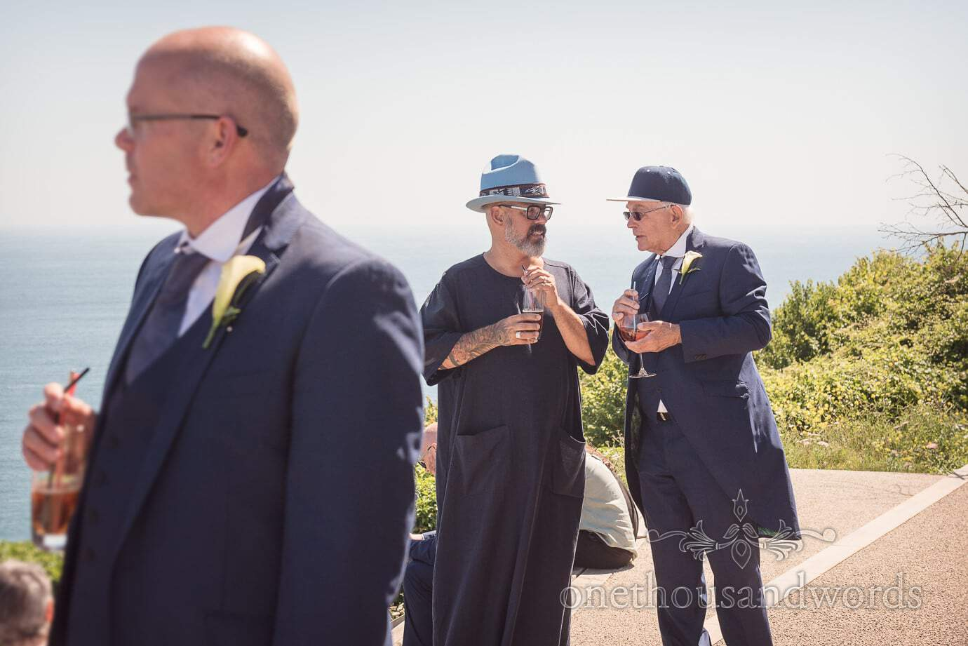Father of the groom in baseball cap talks to wedding guest in big blue hat at drinks reception