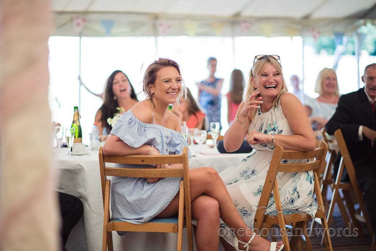 Female wedding guests laugh at wedding speeches in countryside wedding marquee