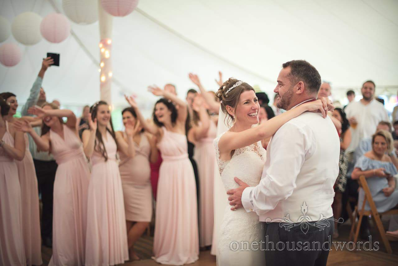 First dance with bridesmaids in pink bridesmaids dresses in background of marquee