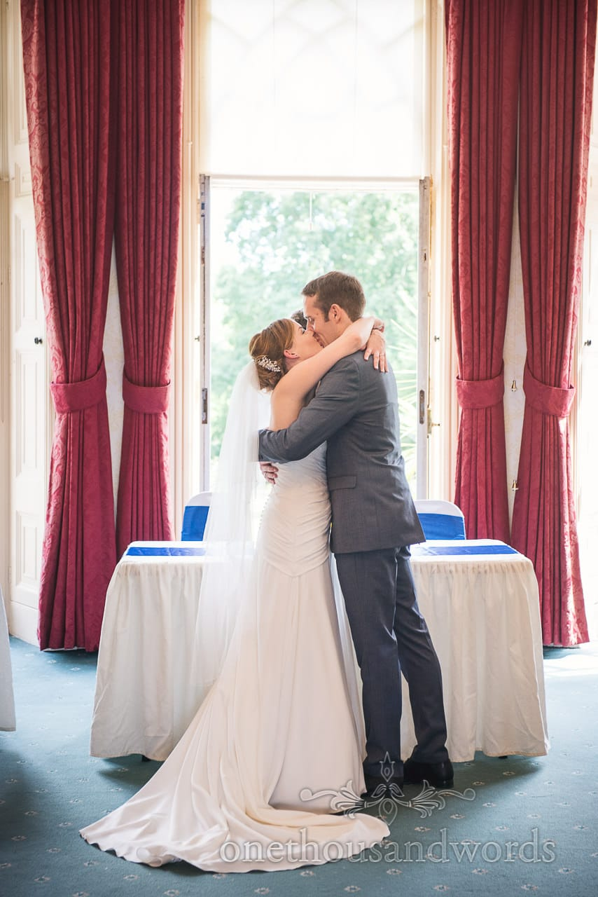 First kiss in front of red curtains at Upton House wedding ceremony in Dorset