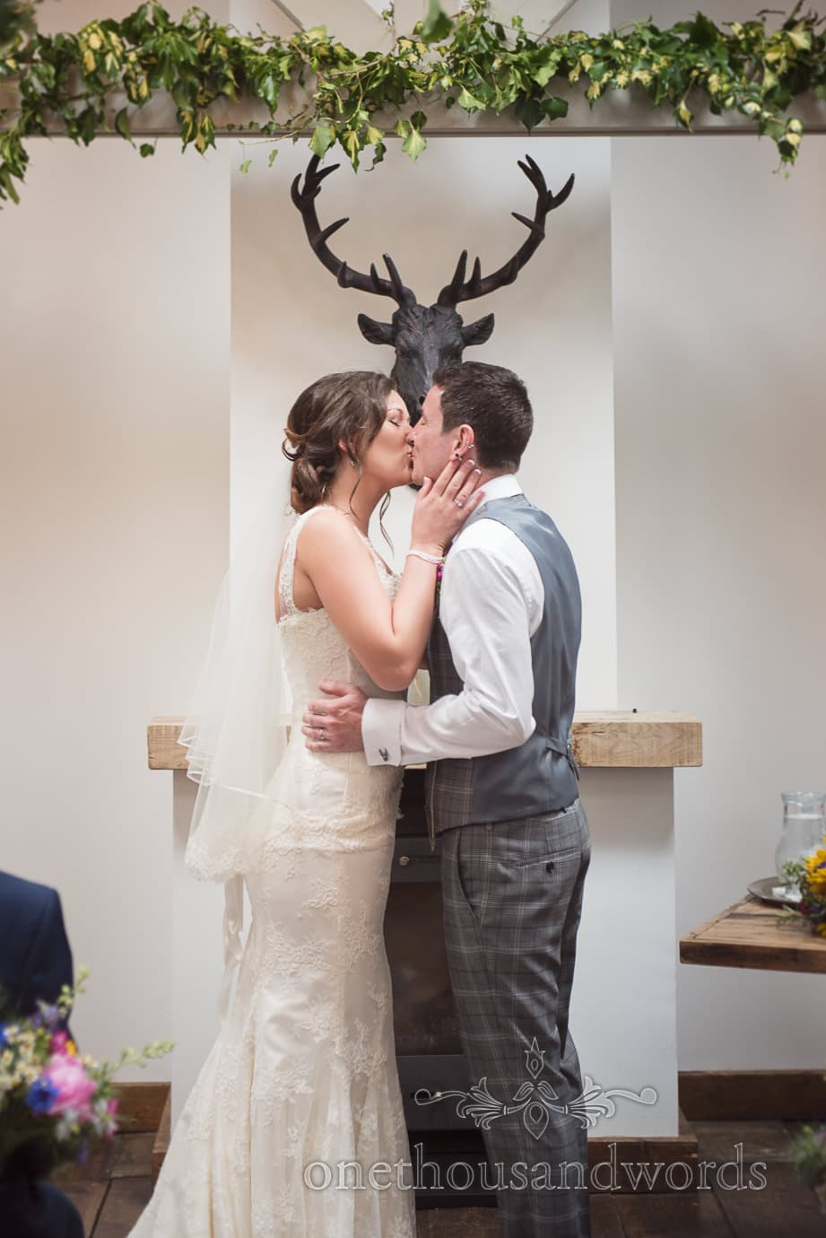 First Kiss under bronze stags head at The Old Vicarage Wedding ceremony