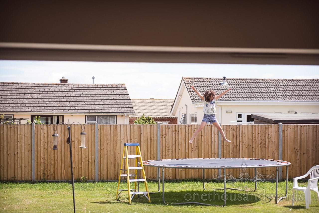 flower girl bounces on trampoline at family home on wedding morning in Dorset