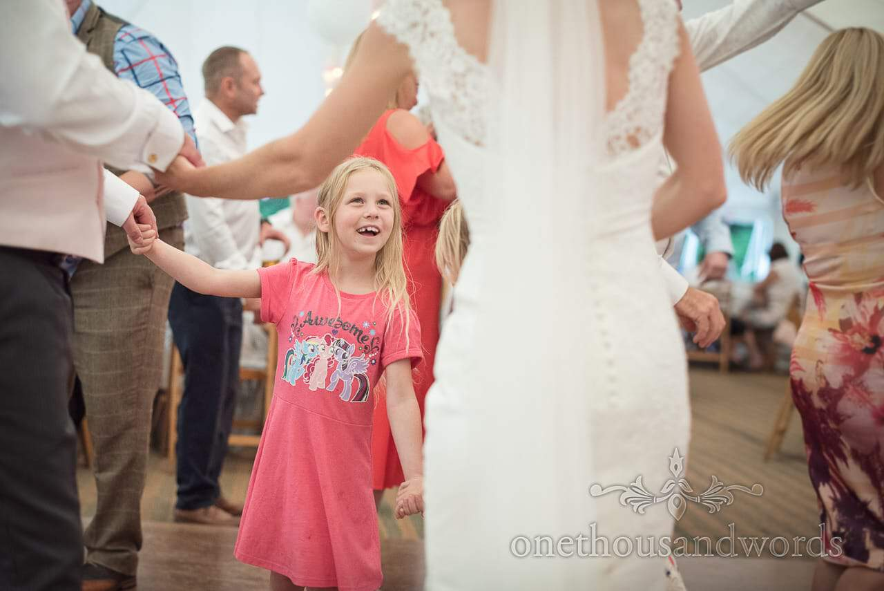 Flower girl in my little pony t-shirt dances with bride at marquee wedding evening reception