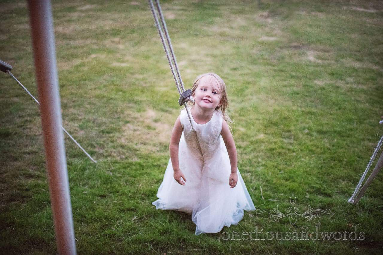 Flower girl in white flower girls dress leans on wedding marquee ropes at country wedding