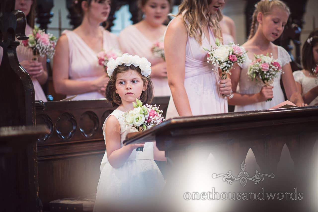 Flower girl surrounded by bridesmaids in pink bridesmaids dresses in church pews