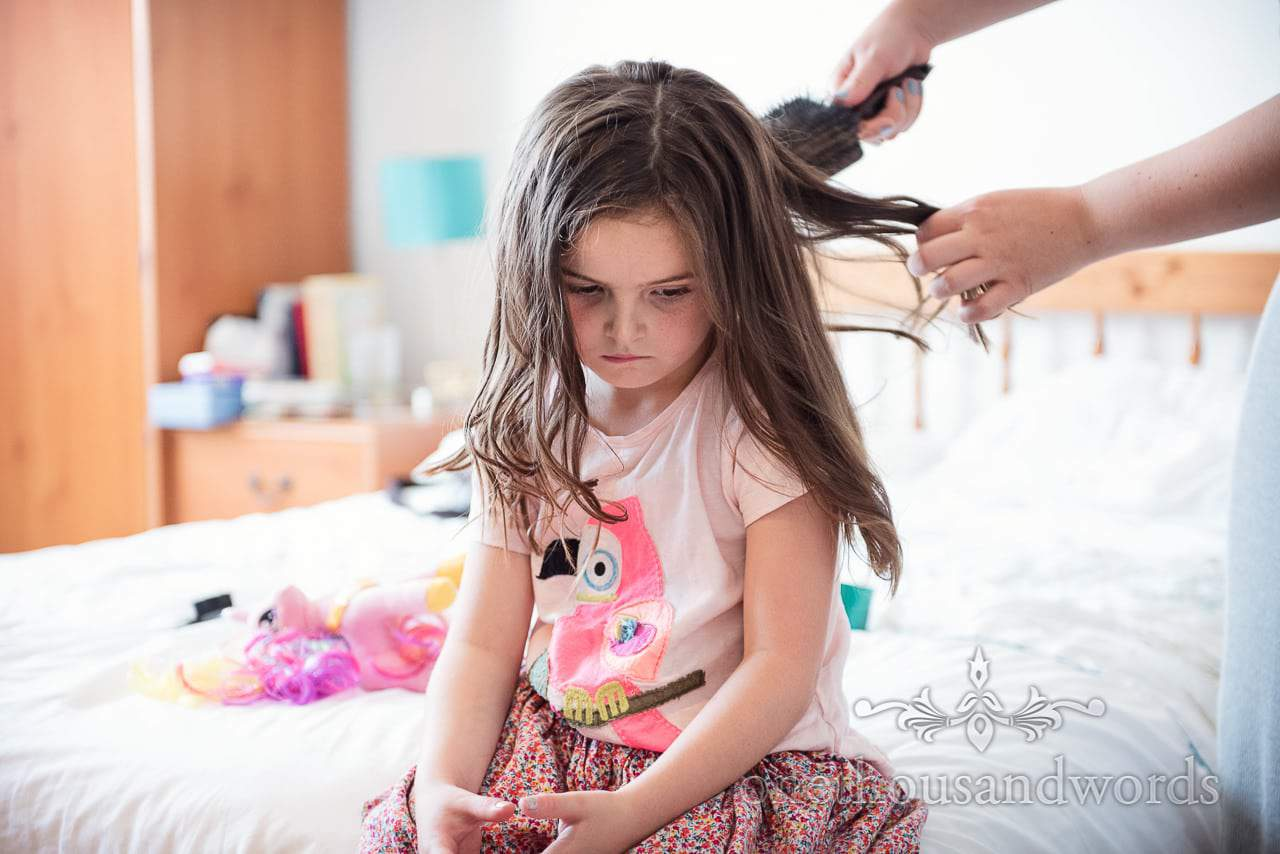 Flower girl with grumpy face has wedding hair styled on wedding morning in Dorset