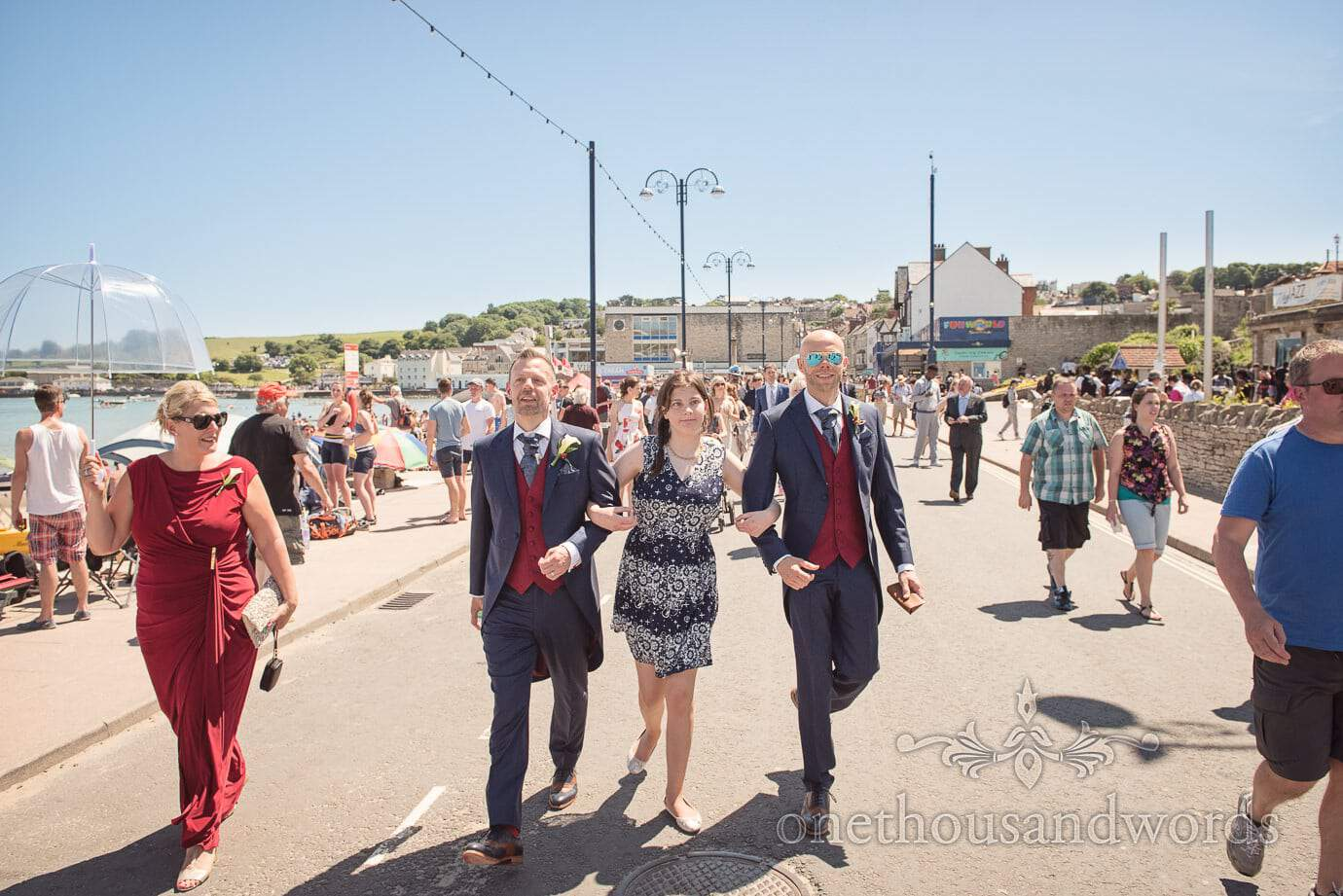 Gay grooms and wedding guests walk along crowded Swanage seafront in summer sun