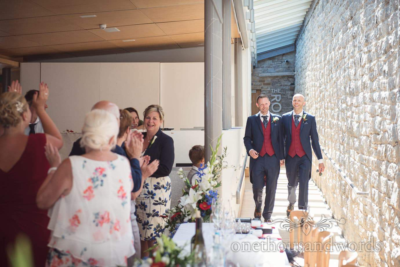 Gay grooms in blue and red suits enter Durlston Castle wedding breakfast