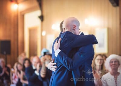 Gay wedding couple hug after wedding ceremony at Purbeck House Hotel in Dorset