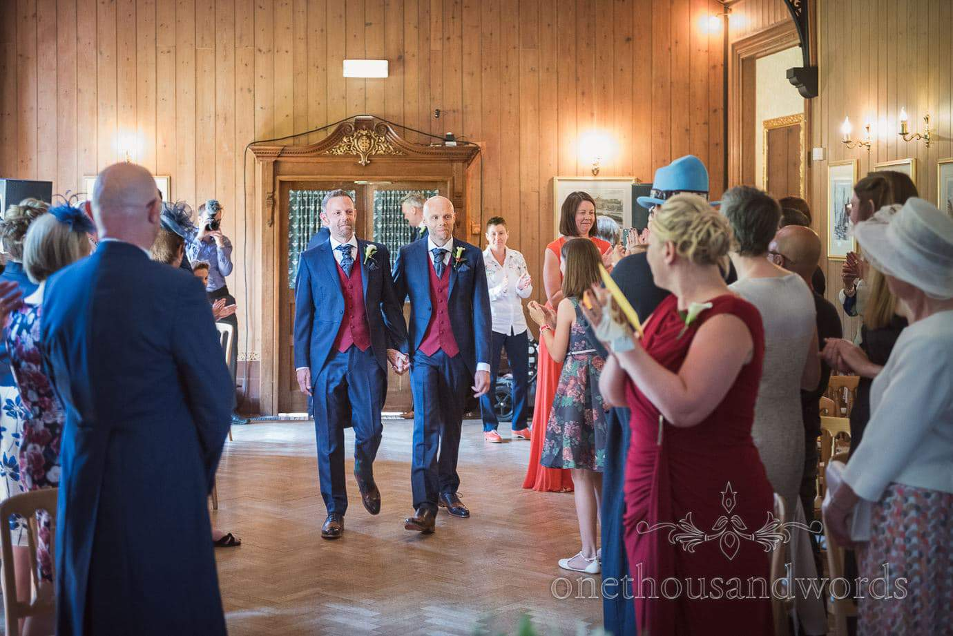 Gay wedding couple in blue and red suits walk up aisle at Purbeck House Hotel wedding