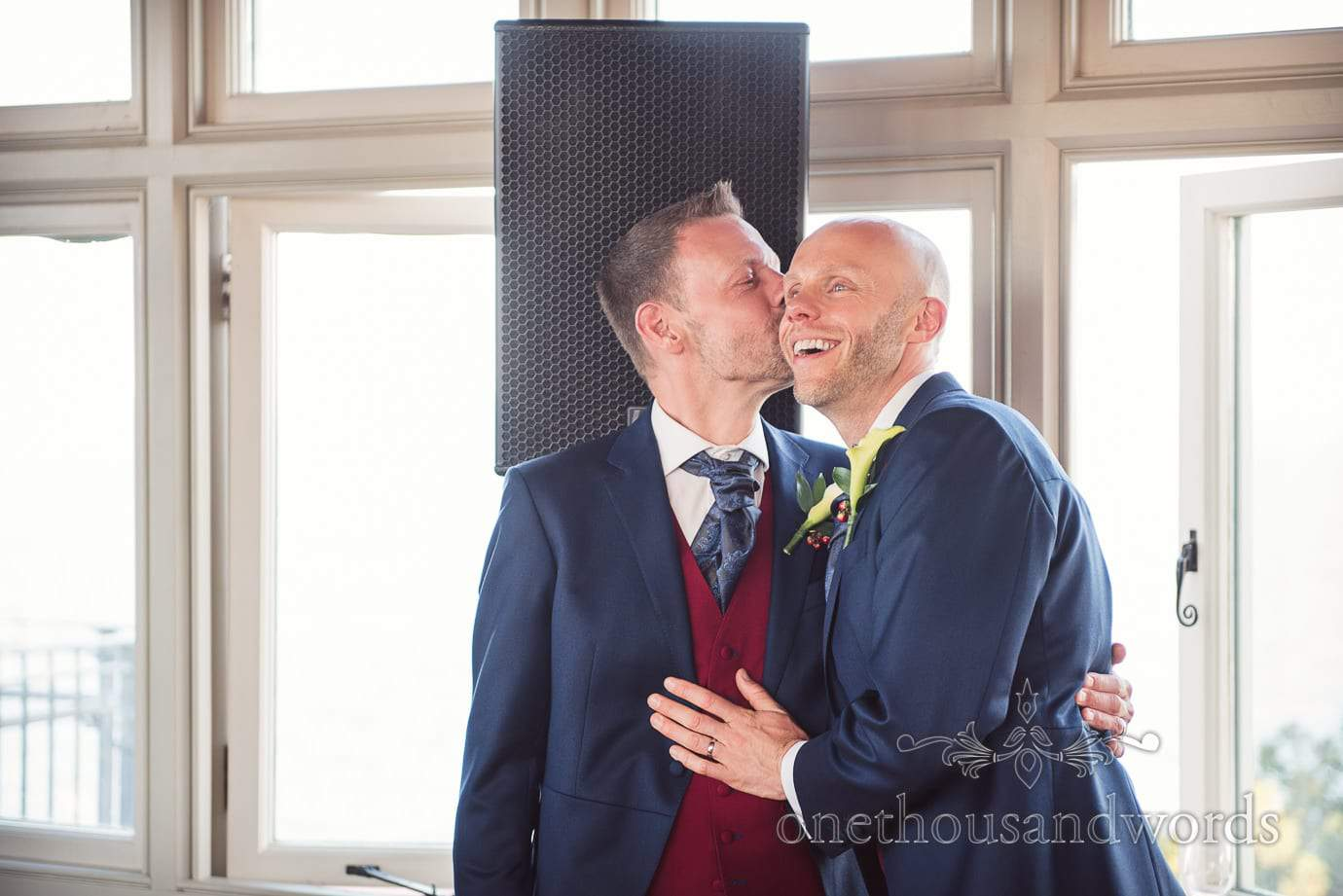 Gay wedding couple in blue suits kiss during wedding speeches at Swanage Castle wedding