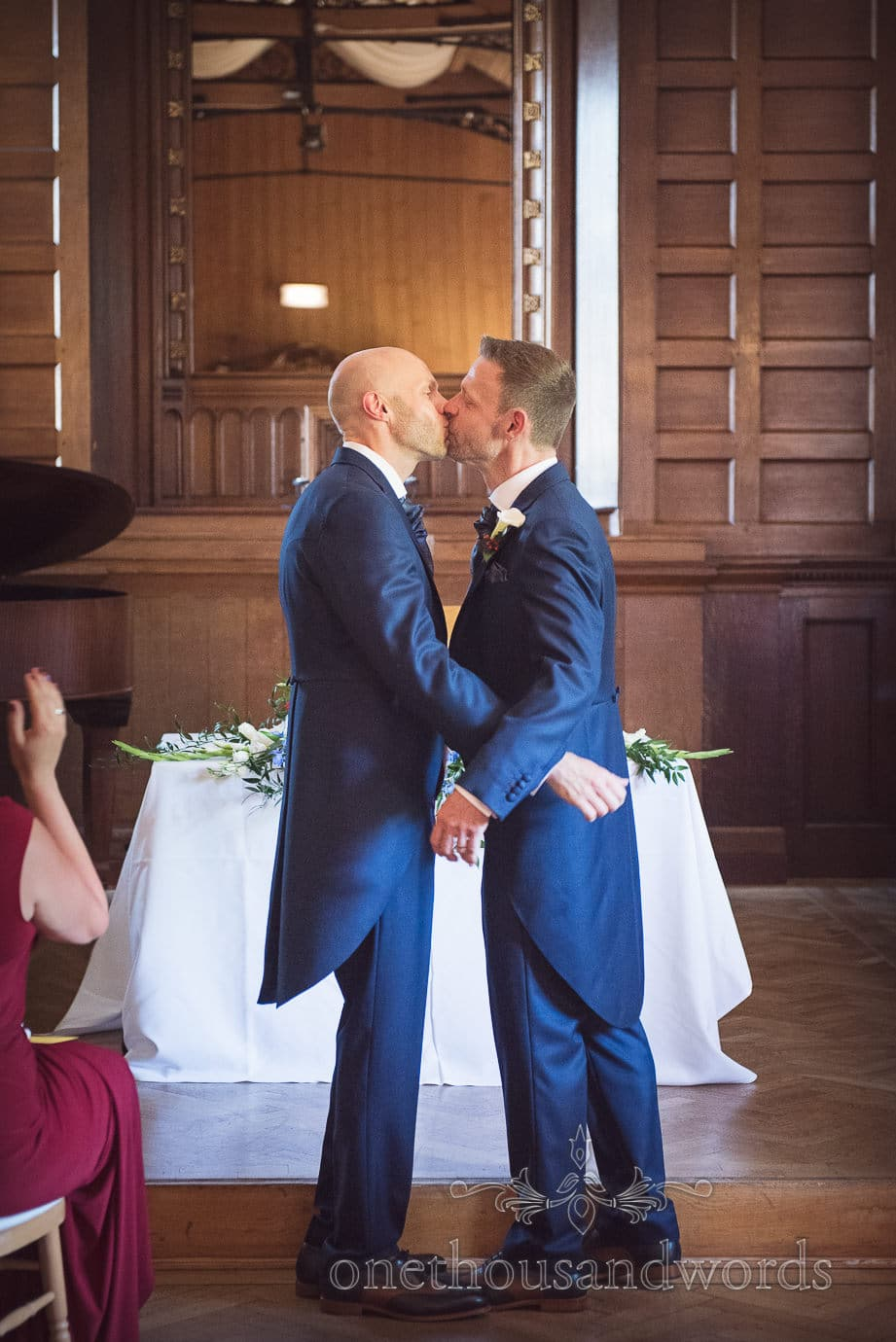 Gay wedding couple in blue wedding suits kiss at Purbeck House Hotel, Swanage
