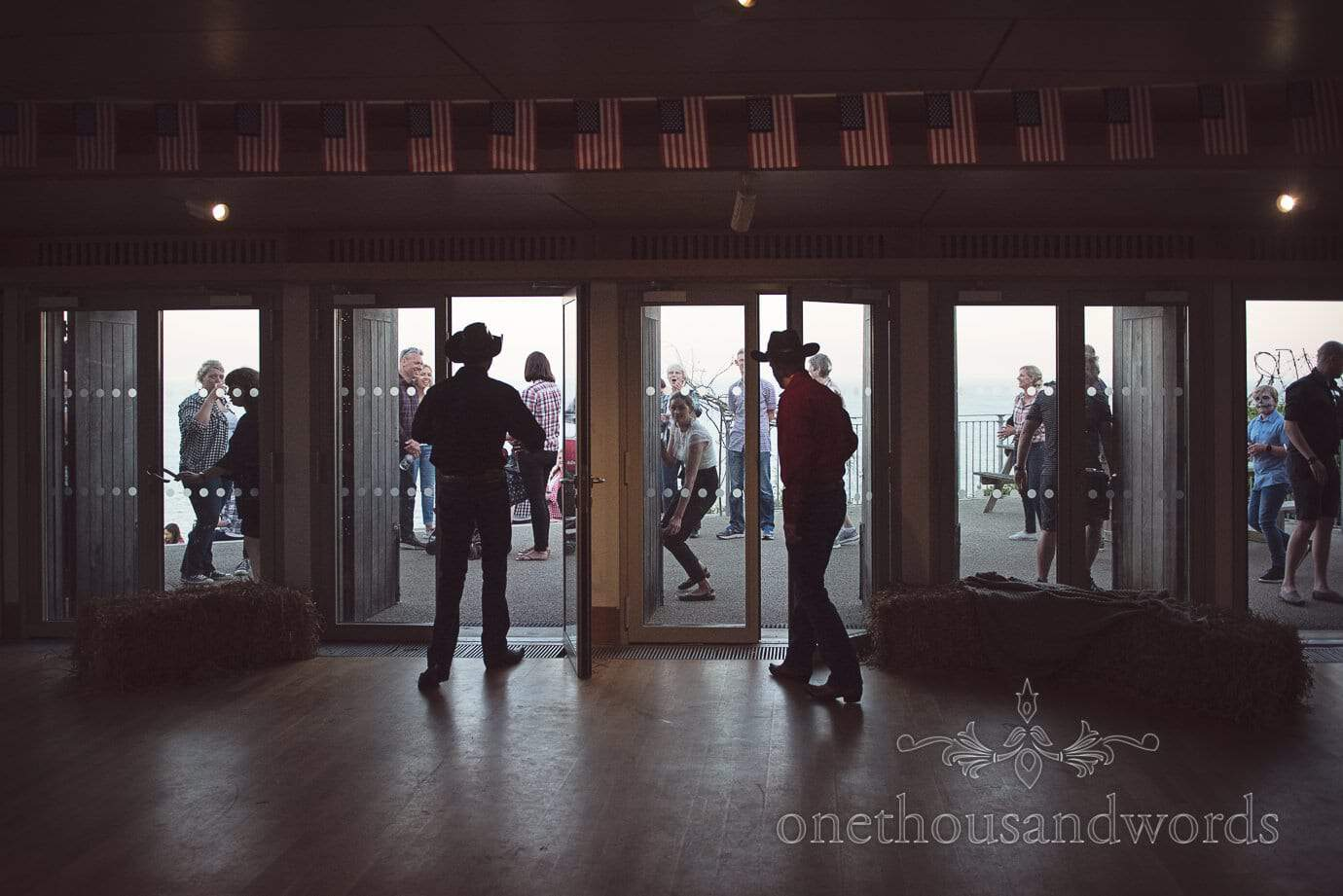 Gay wedding couple in cowboy outfits silhouette reveal surprise wedding barn dance