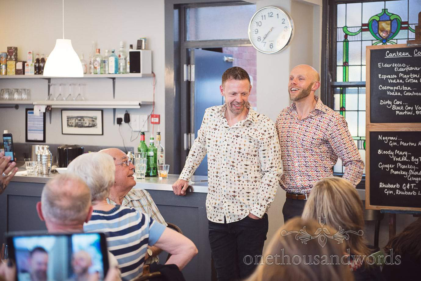 Gay wedding couple in patterned shirts give speech at pre-wedding meal in Swanage