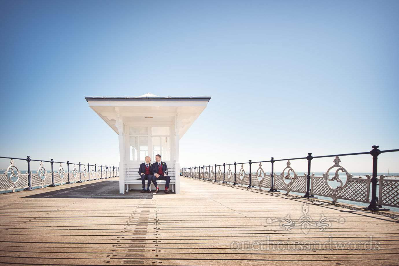 Gay wedding couple in white shelter on Swanage Victorian pier on Summers wedding