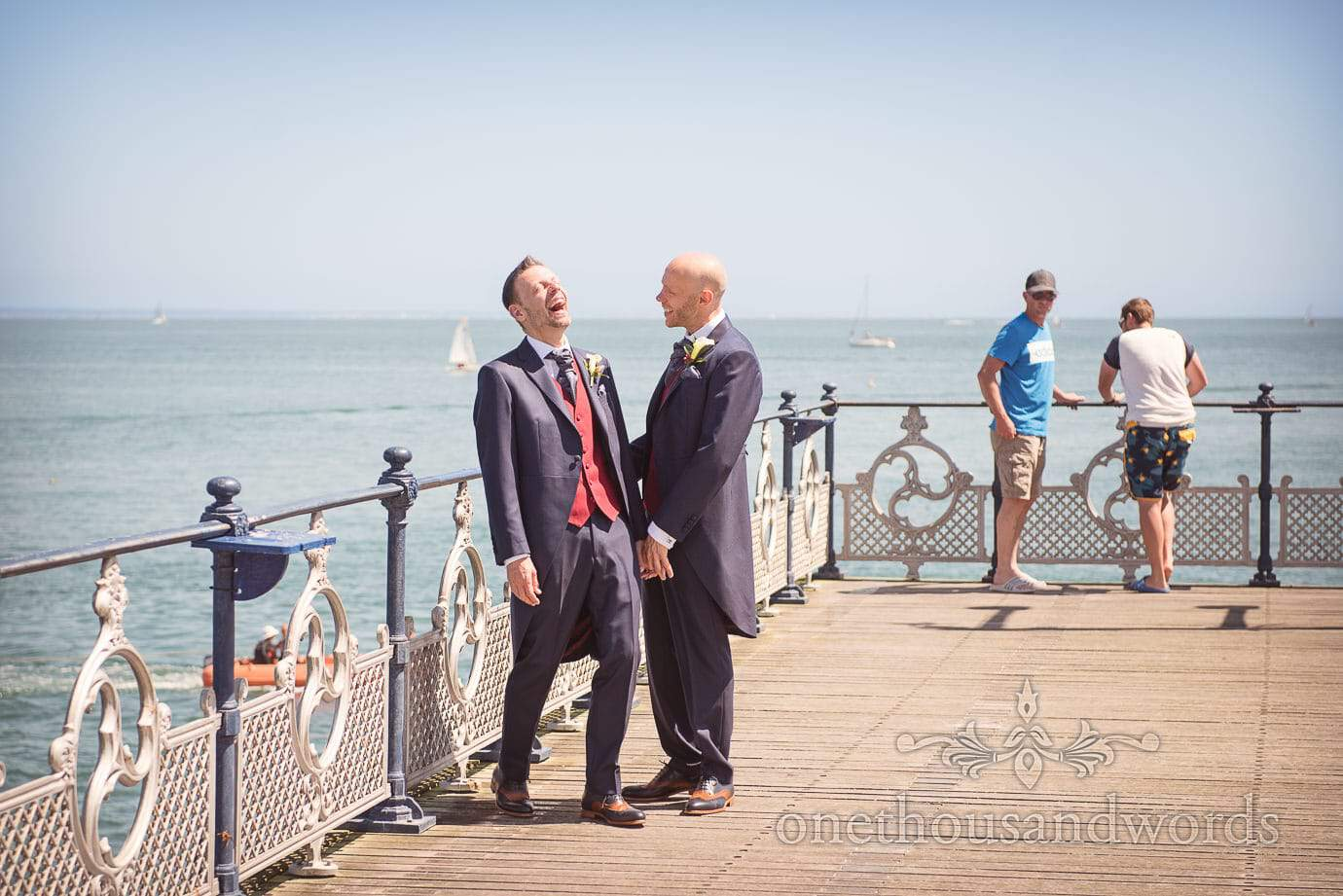 Gay wedding couple laughing on Swanage Victorian Pier on Summers Day