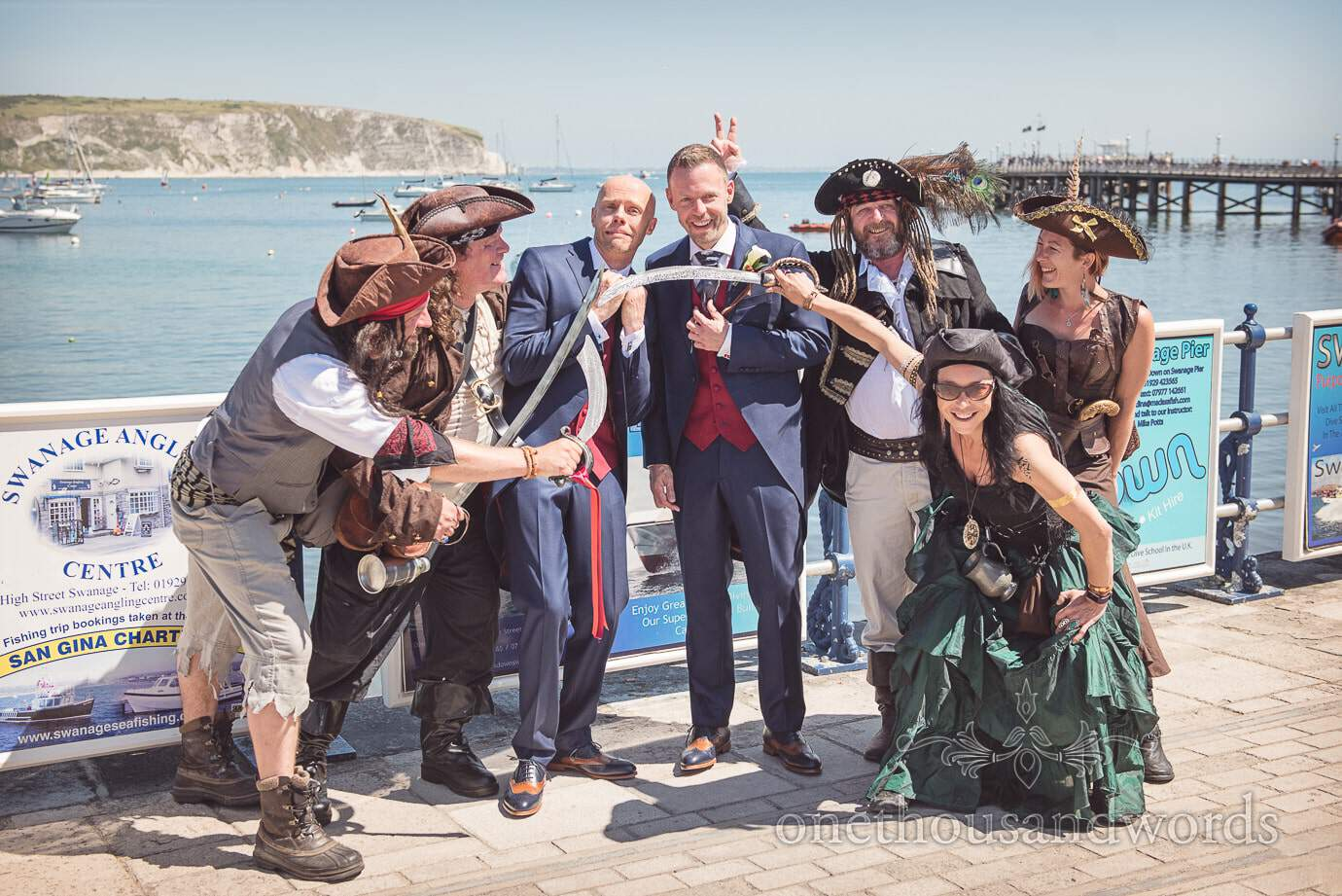 Gay wedding couple with Swanage pirates on sea front with Swanage Pier