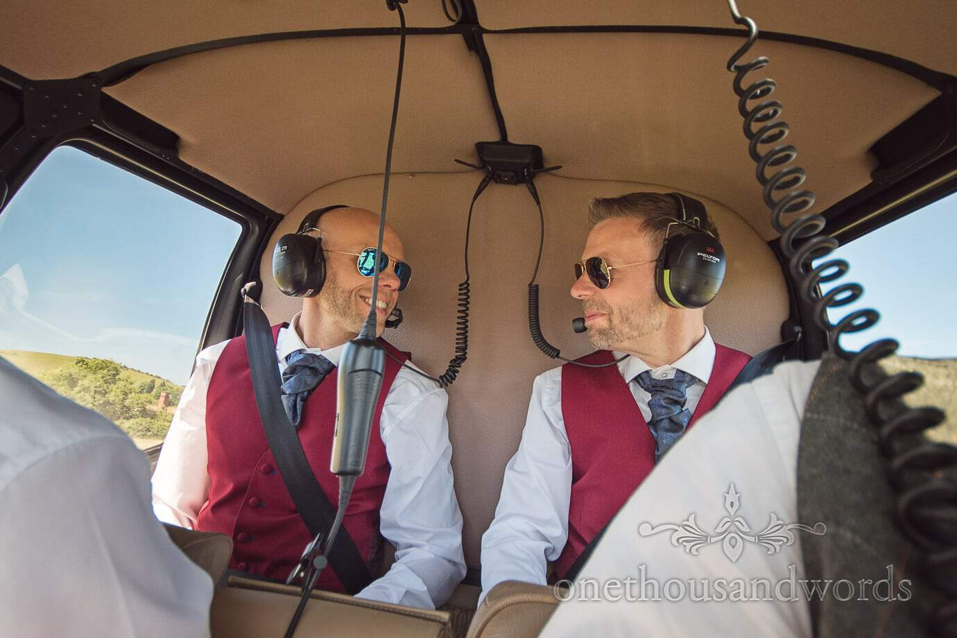 Gay wedding grooms in red waistcoats and headphones helicopter ride over the Dorset coast