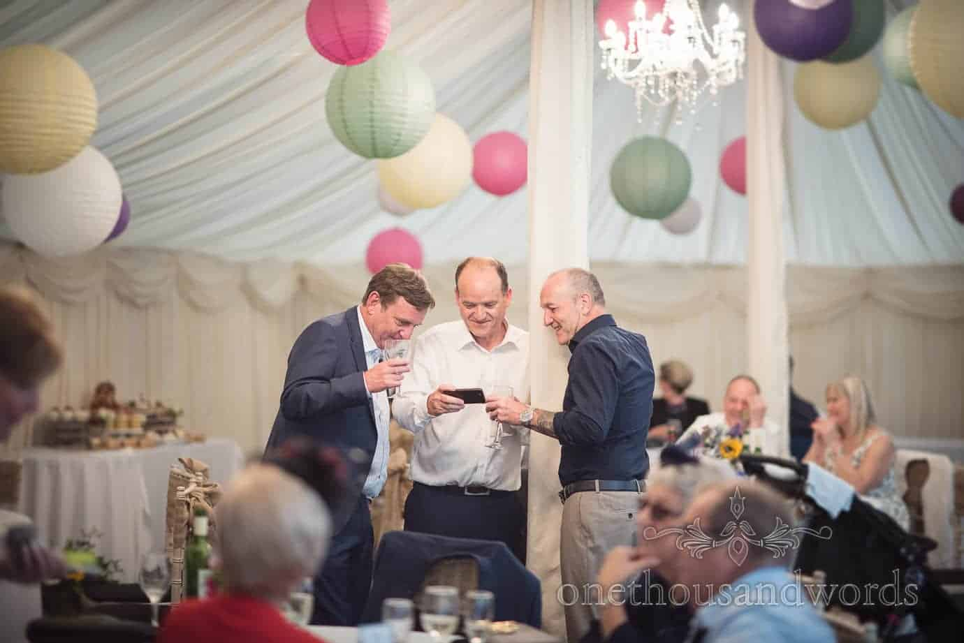 Gentleman wedding guests look at mobile phone in The Old Vicarage Wedding marquee