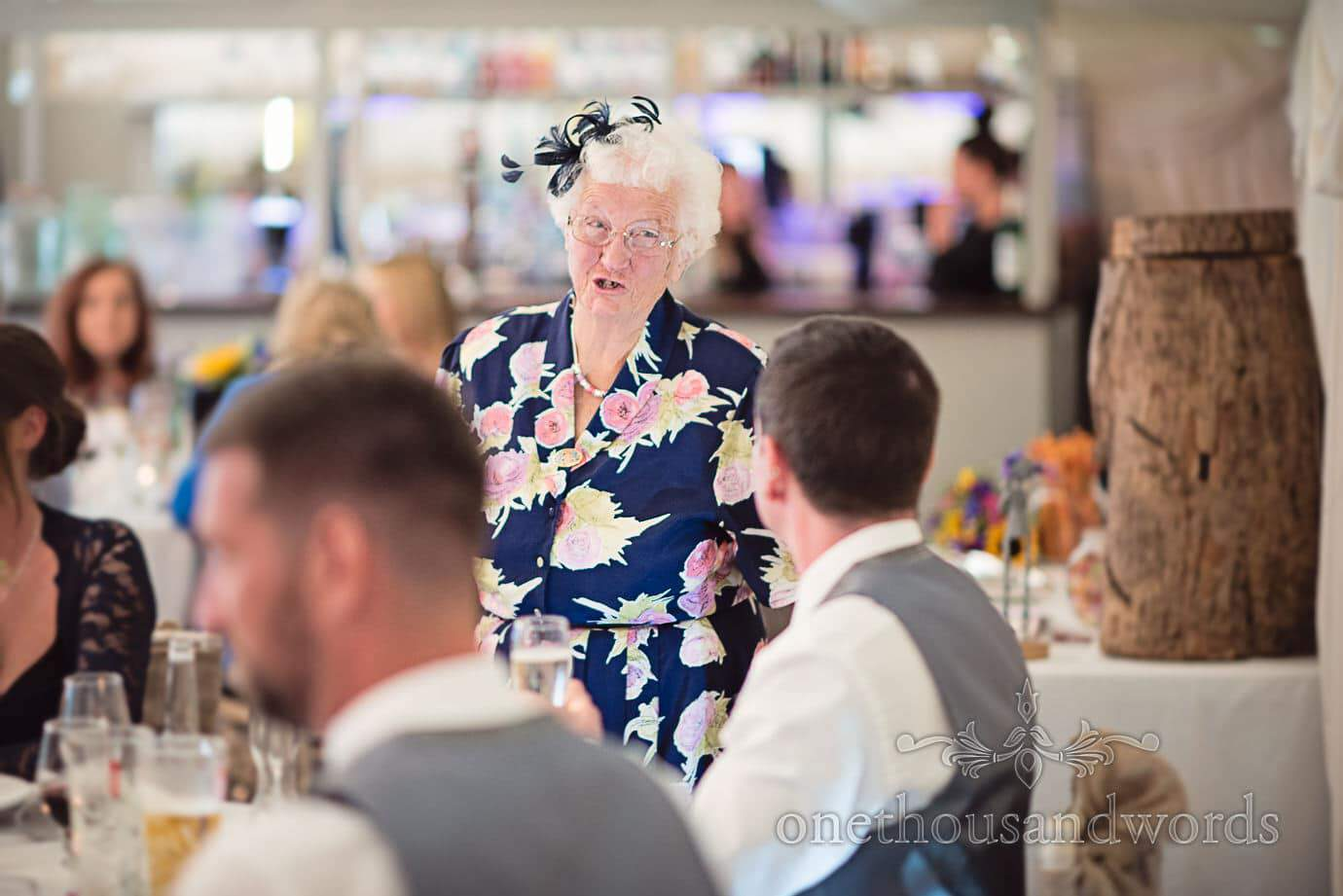 Grandma in floral dress and fascinator talks to groom at The Old Vicarage Wedding