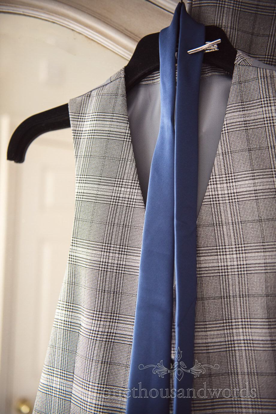 Grey prince of Wales check waistcoat with blue tie hanging on wedding morning