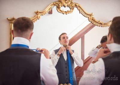 Groom and groomsmen tying blue wedding ties in gold gilded mirror
