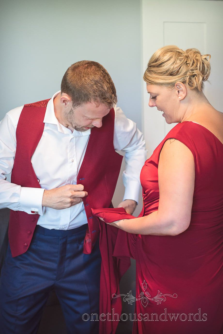 Groom and maid of honour compare red wedding clothing on Swanage wedding morning