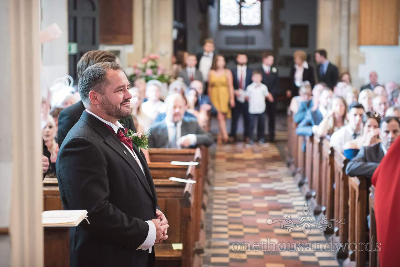 Groom in black wedding tail suit awaits arrival of the bride in English stone church