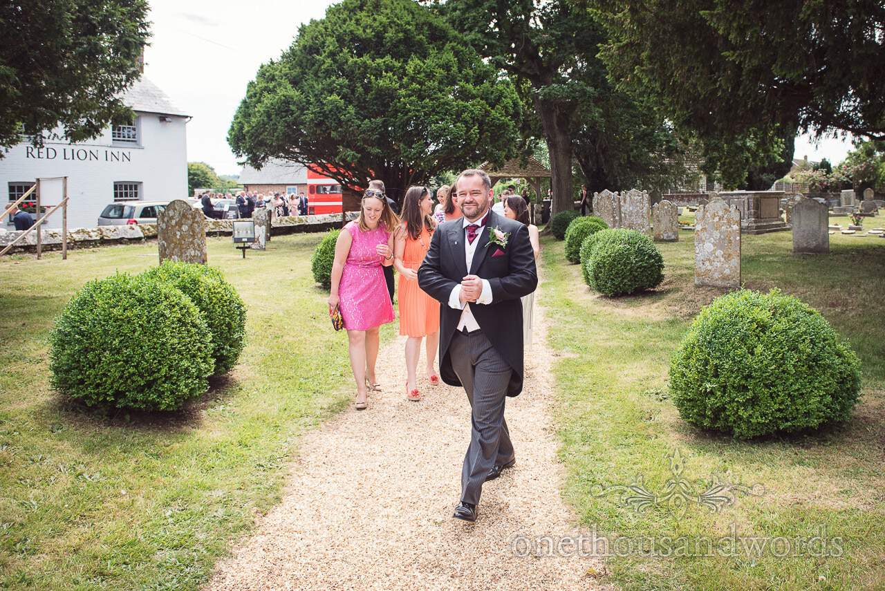 Groom in black wedding tails in church grounds outside Red Lion Inn in Dorset