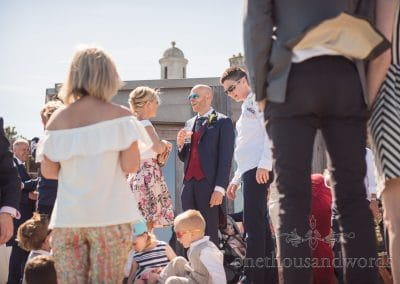 Groom in blue and red suit at Durlston castle wedding drinks reception in the sun