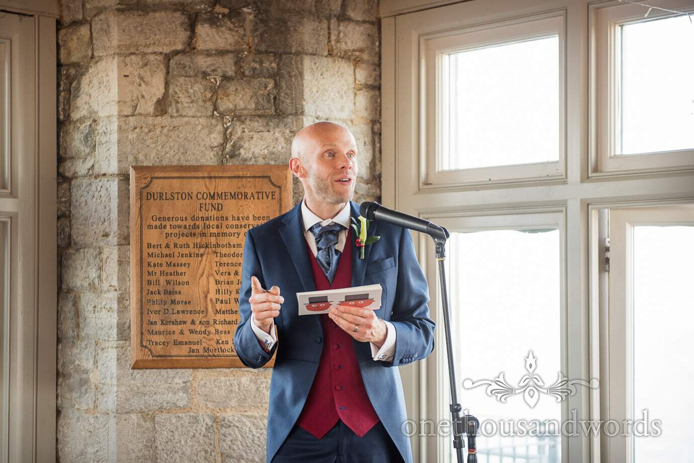 Groom in Blue and red wedding suit gives groom's speech at Durlston Castle wedding venue