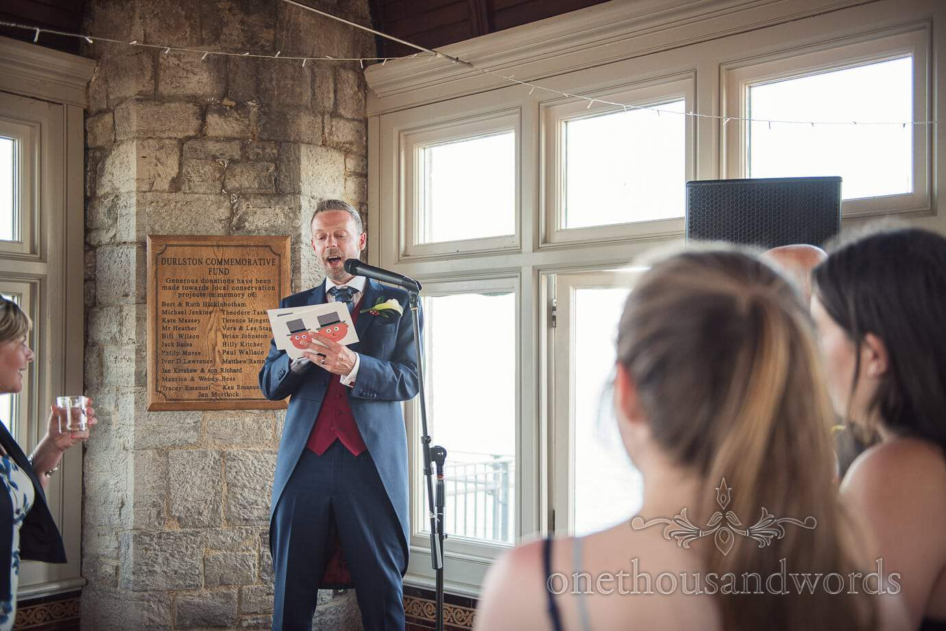 groom in blue suit reads wedding speech from custom cartoon speech cards at Durlston Castle